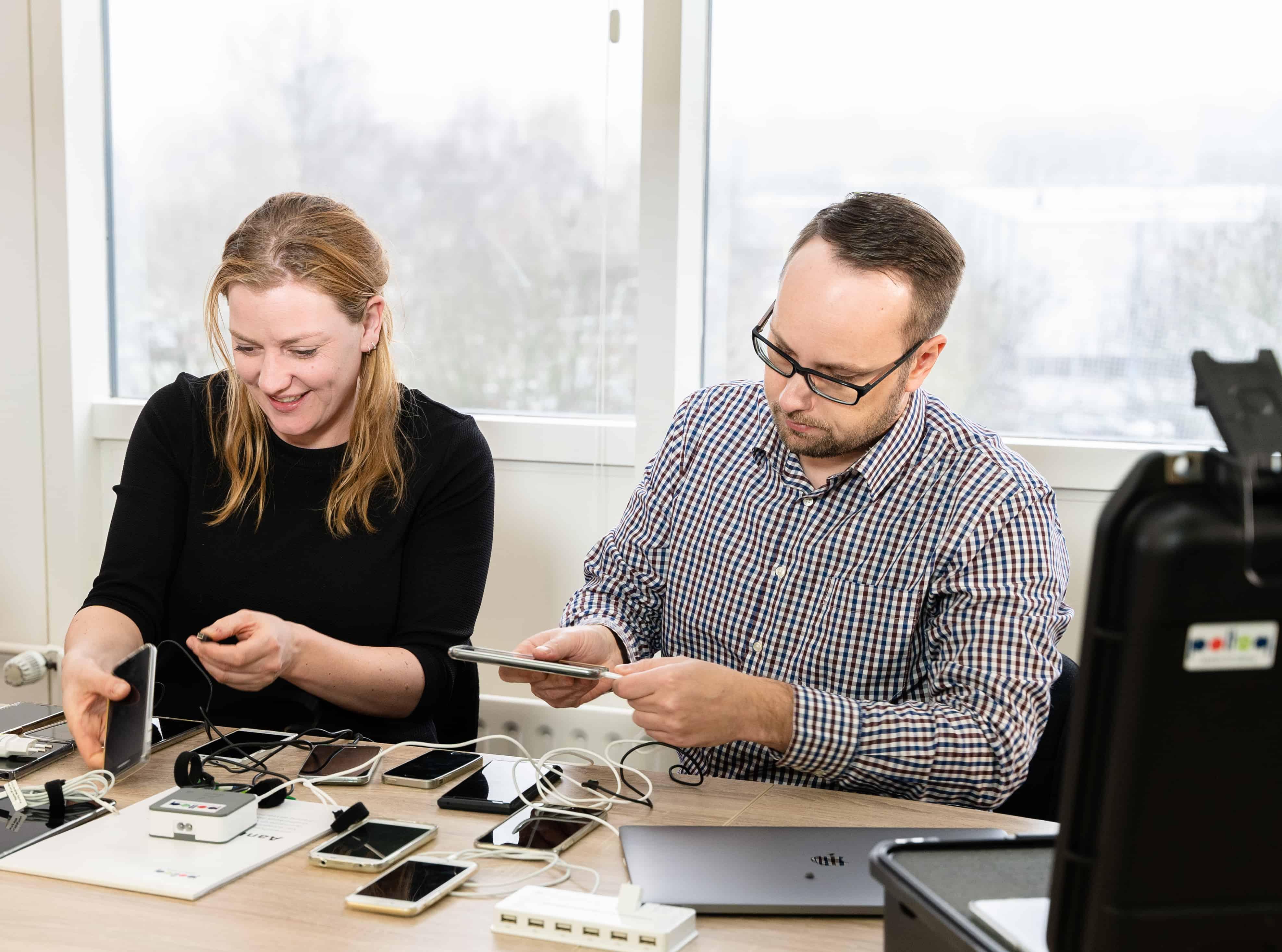 Twee testers zijn mobiele telefoons aan het aansluiten