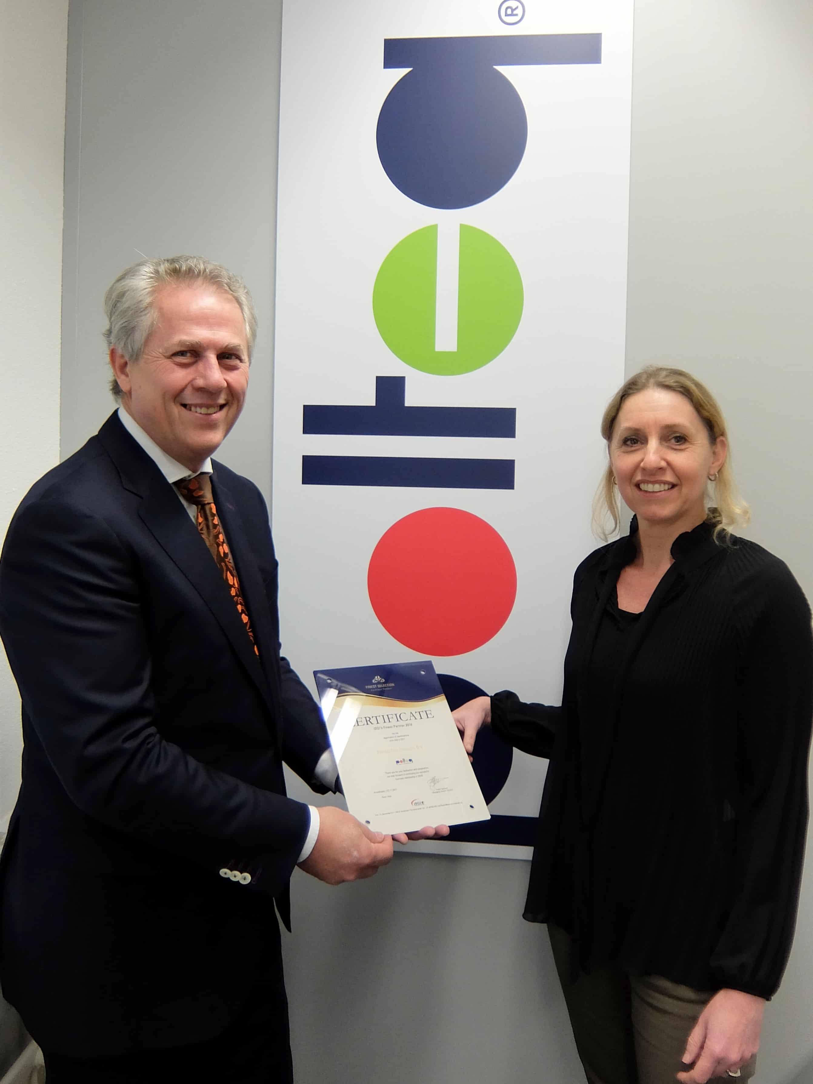 Frank Frambach, Managing director iSQI Netherlands, overhandigt de award aan Anja Bakker, Manager Opleidingen van Polteq.